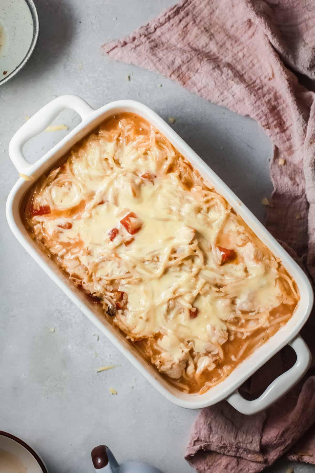 chicken Spaghetti Casserole in a white baking dish with a purple hot pad
