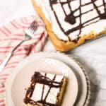 Shot of the top of a cream puff square cake with a full cake in the background and a fork and napkin