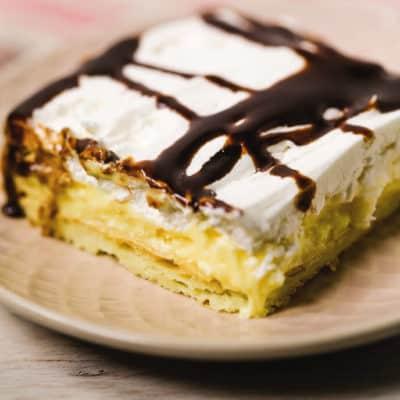 Cream Puff Cake square on a peach plate