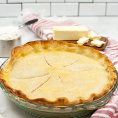 Crisco Pie Crust ina glass pie dish with ingredients and a red and white stripped napkin