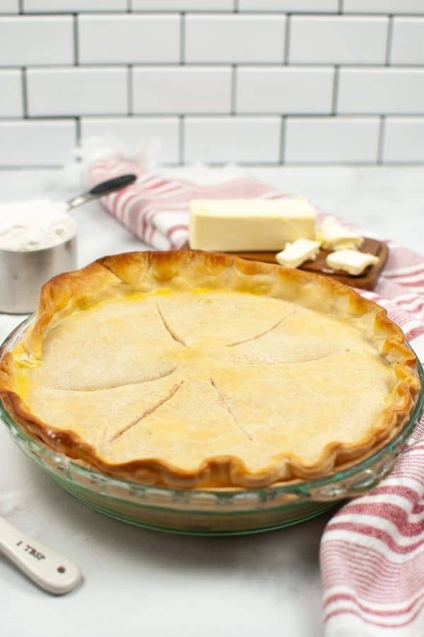 Crisco Pie Crust in a glass pie dish with ingredients and a red and white stripped napkin .