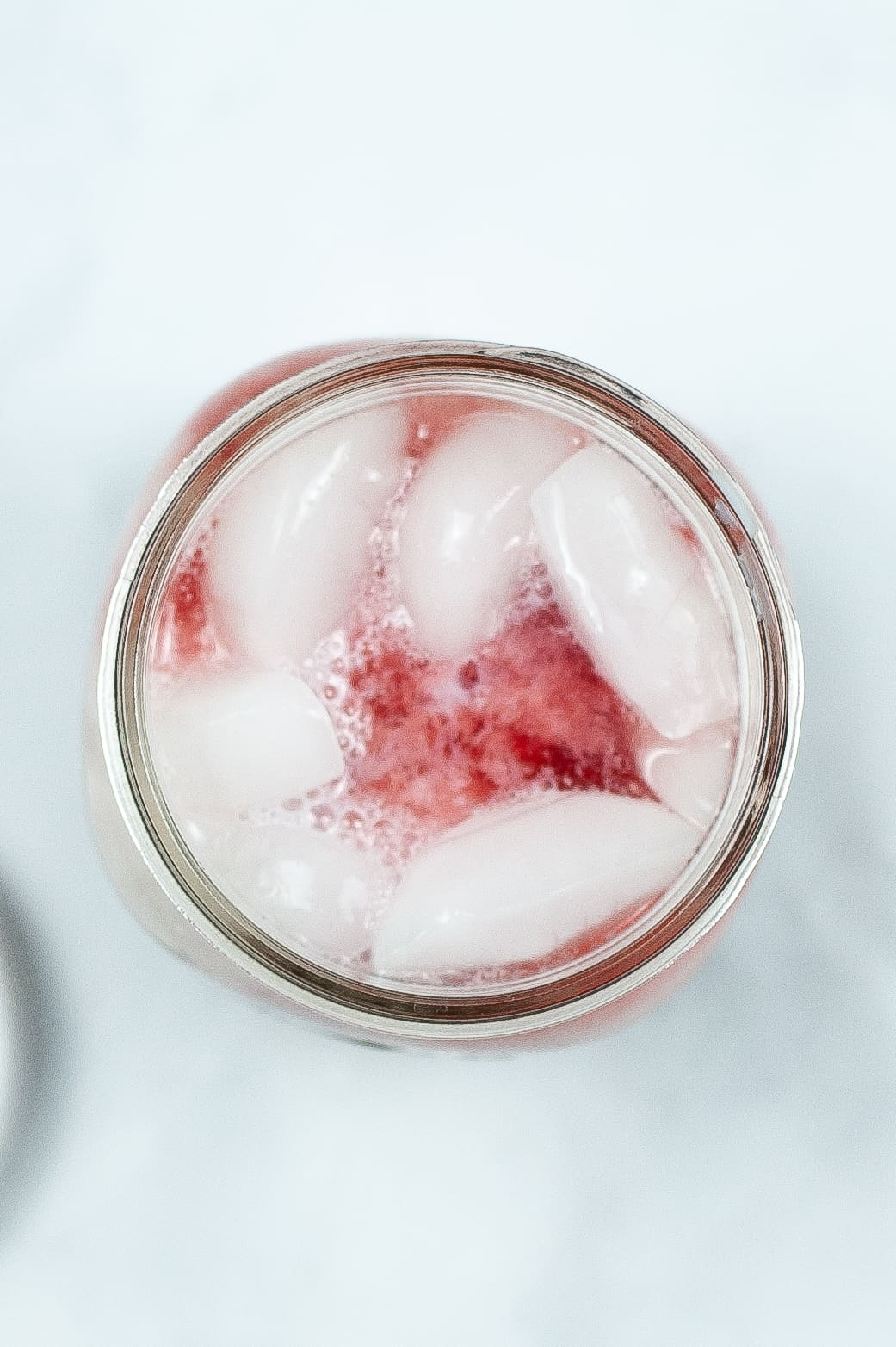 Tip shot of pink drink with ice.