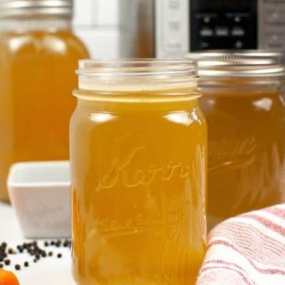 Canning Jar with bone broth with white bowl and peppercorns and other jars