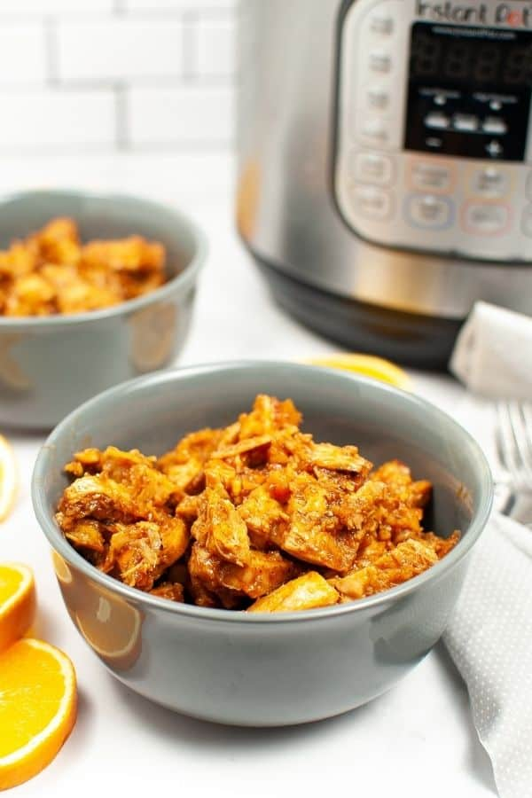 Instant Pot Orange Chicken in a Gray bowl with an instant pot in the background