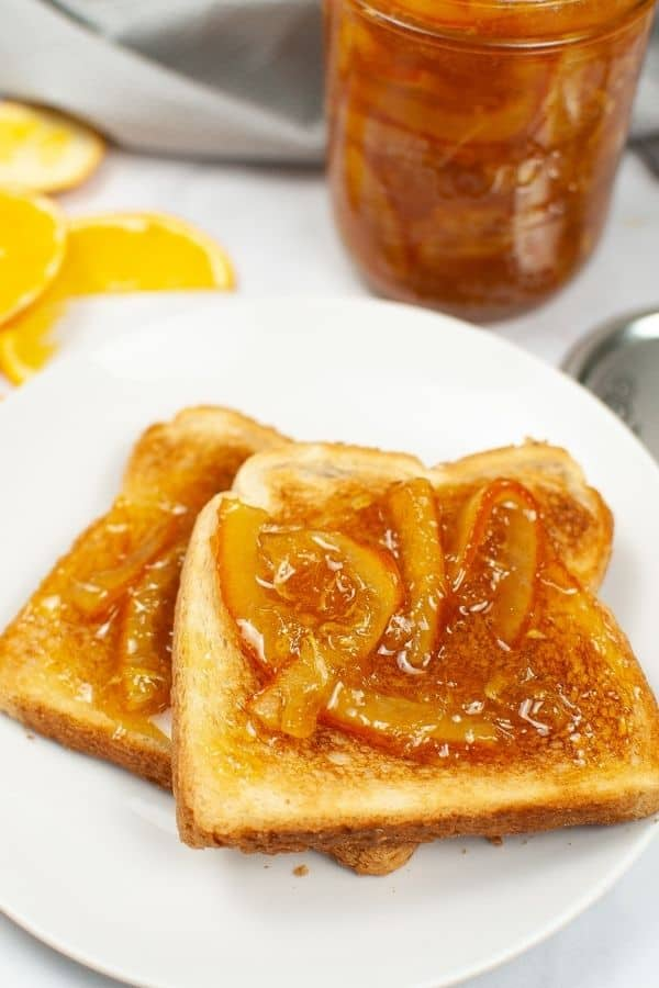 Toast with Orange Marmalade on it on a white plate