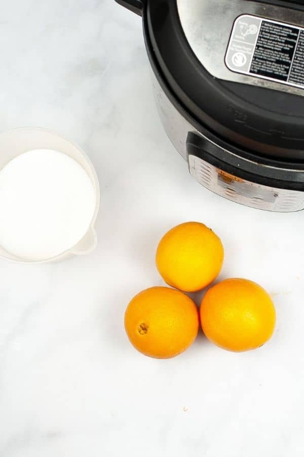 oranges and sugar next to an instant pot
