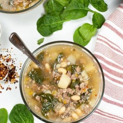 Top shot of Instant Pot Sausage and spinach soup with spinach and Instant pot in backgroup
