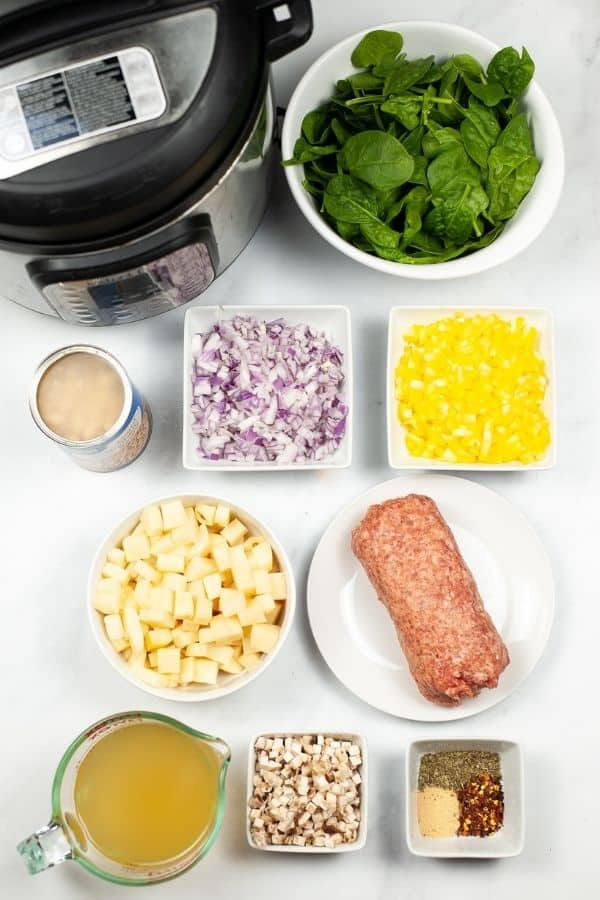 Instant pot woth ingredients of onions peppers spinach sausage broth and herbs.