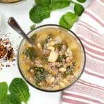 Italian and Sausage soup in a glass bowl with a pink and white stripe napkin with spinach