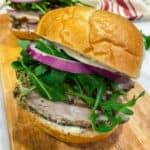 Close up of a porchetta sandwich on a wooden cutting board