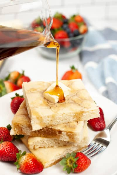 Sheet Pan Pancakes with butter and strawberries, with syrup being poured on them