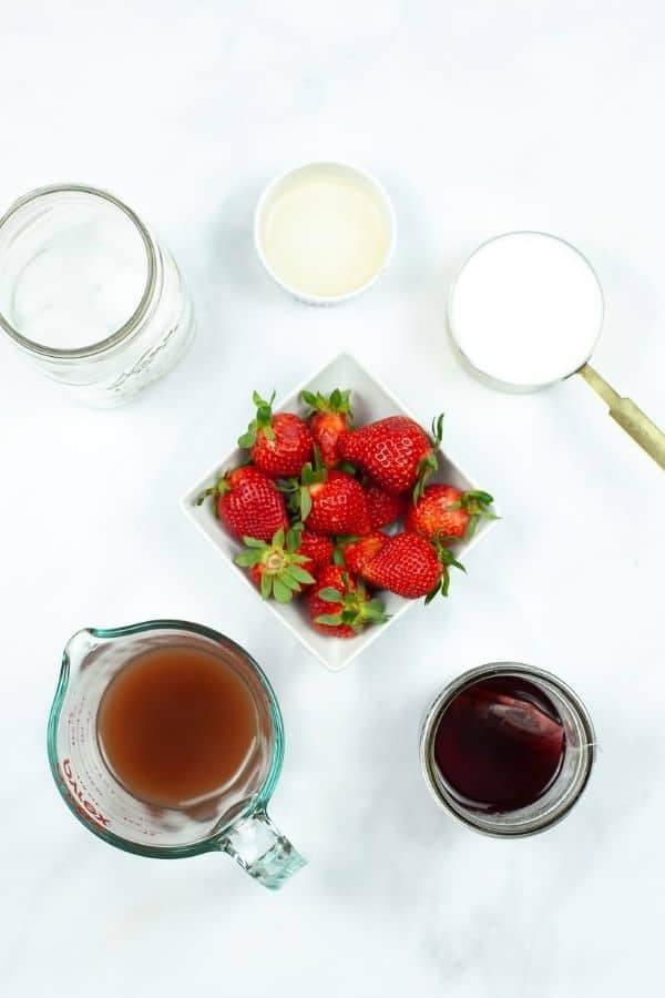 Fresh strawberries, coffee and syrup needed to make pink drink.