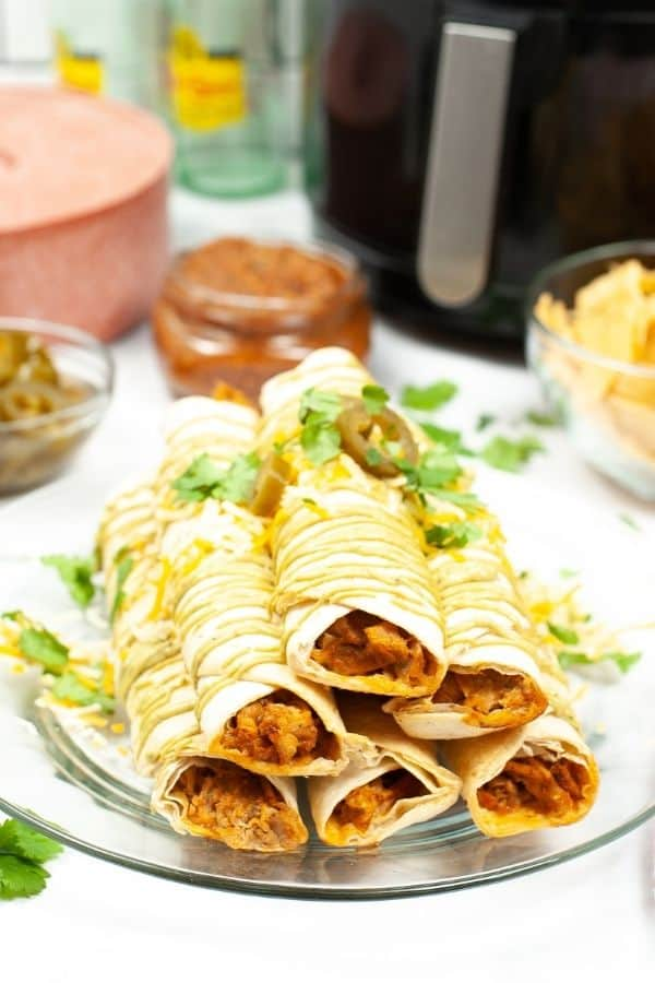 Six Air Fryer Chicken Taquitos stacked on a plate with fresh herbs on top.