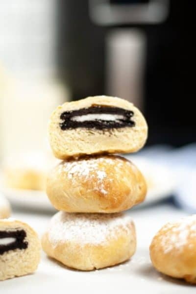 Air Fried oreos stacked on a plate with a cut open one on top revealing the oreo.