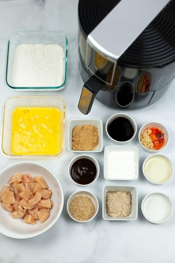 Air Fryer surrounded by bowls of chicken and other ingredients to make sesame chicken.