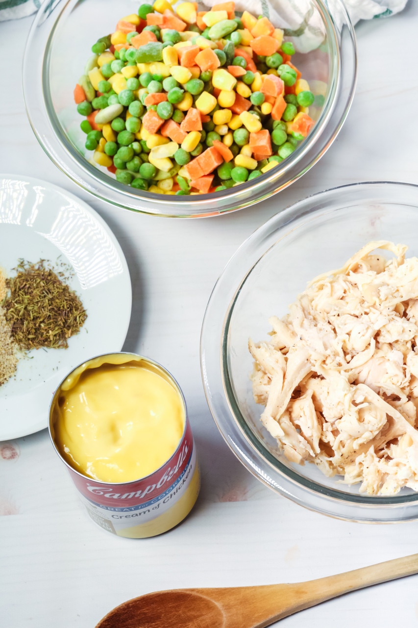 A wooden spoon chicken soup, chicken and vegetables along with bisquick.