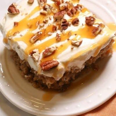 CARROT CAKE POKE CAKE ON A WHITE PLATE