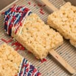 Close up of dipped rice krispy pops with drizzles of red white and blue chocolate.