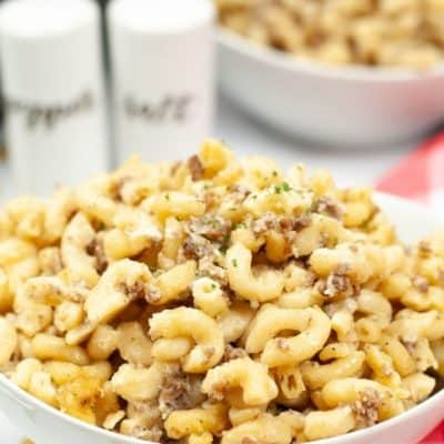 White bowl with cheeseburger macaroni with white salt and pepper shakers on a red and white check tablecloth.