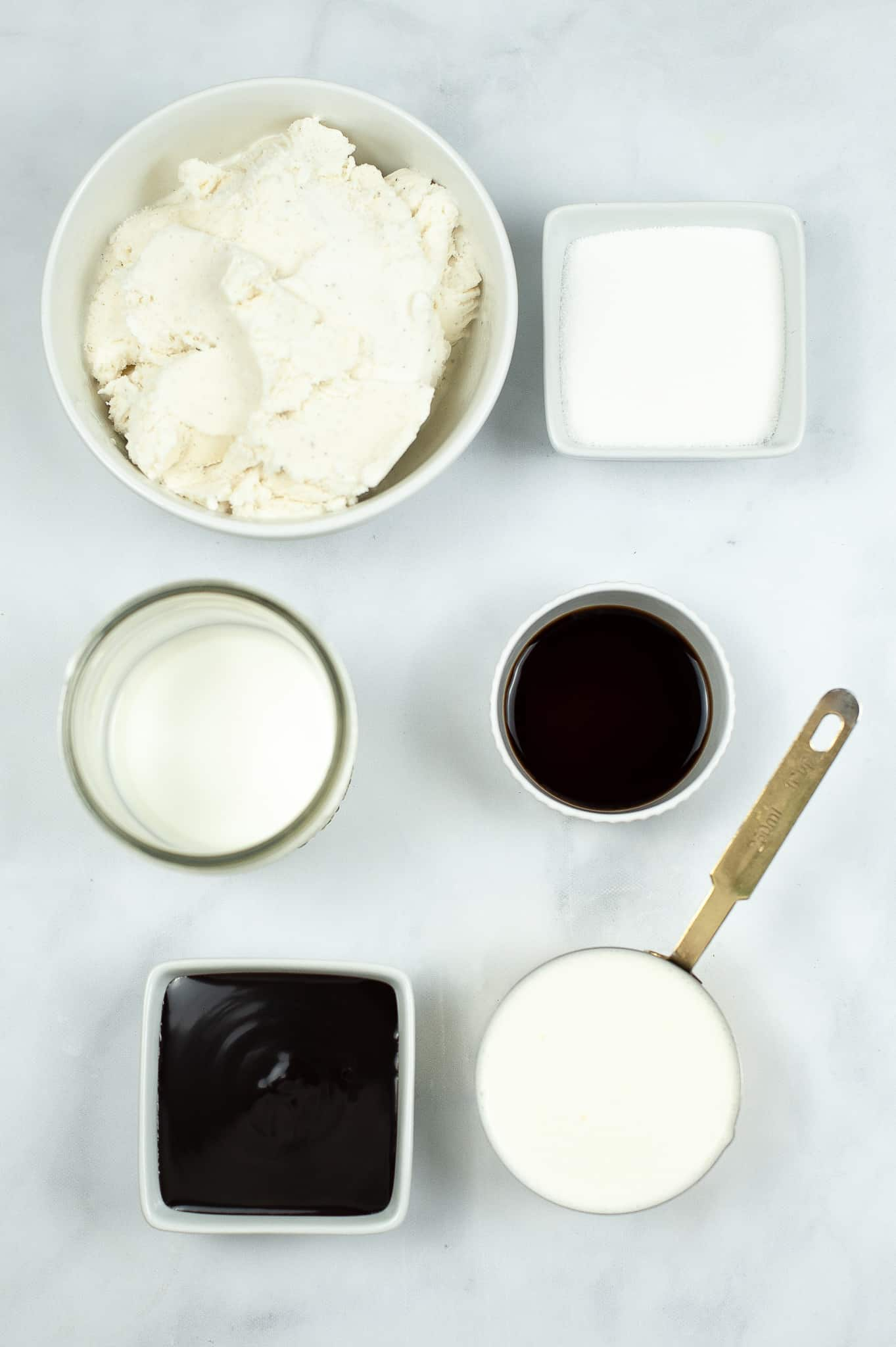Glass dishes with ice cream, milk, chocolate chips and vanilla.
