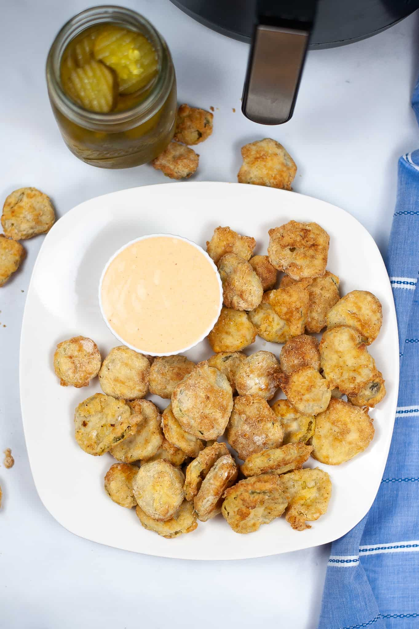 White plate of fried pickles with dipping sauce.