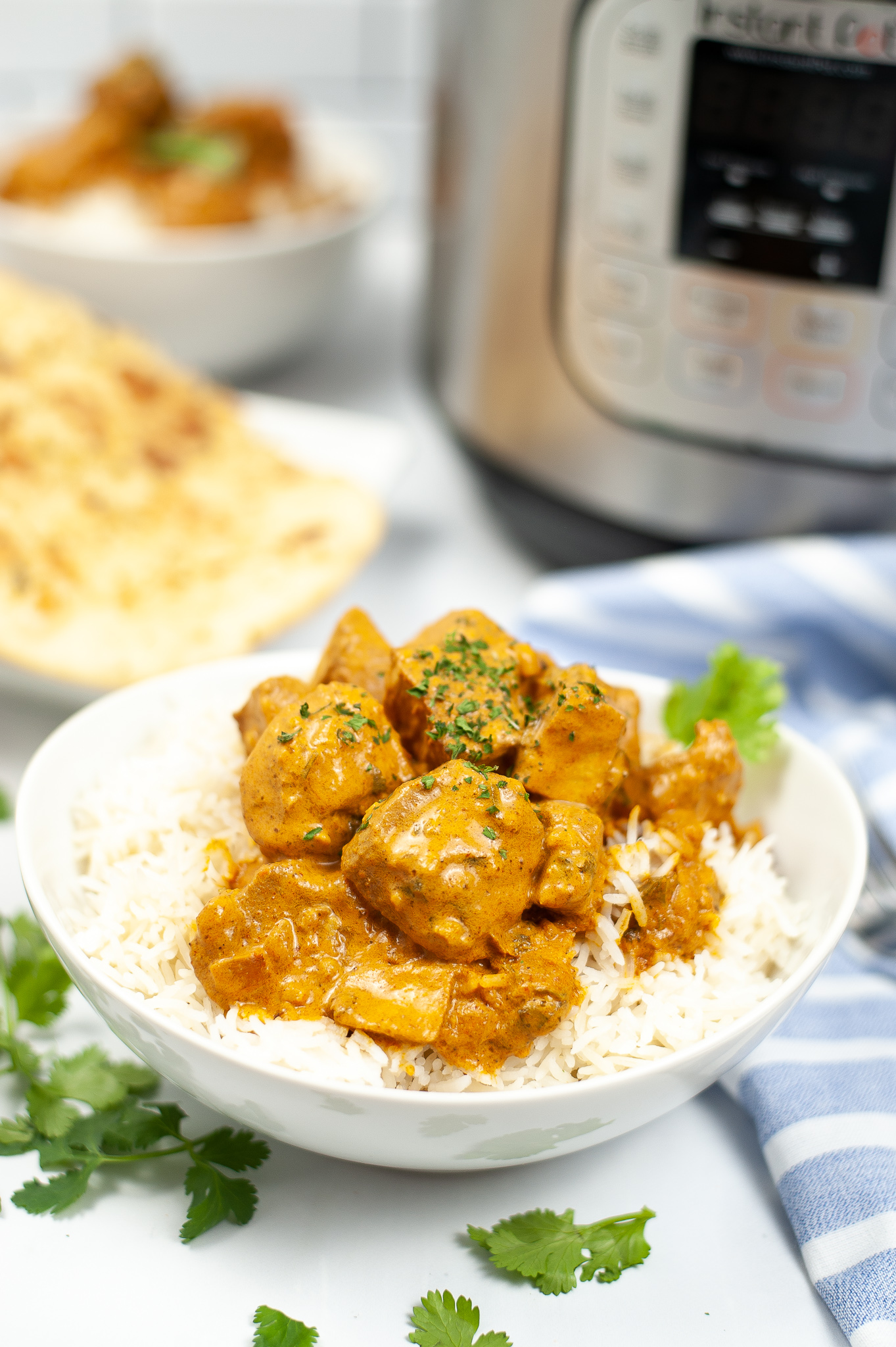 Side view of Instant Pot Butter Chicken in a white bowl. Served over white rice.