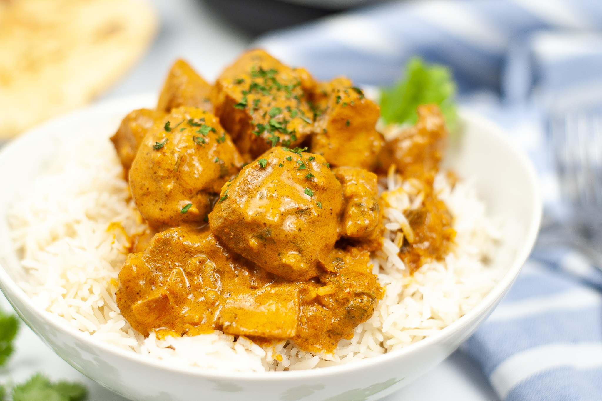 Close up of Butter Chicken over white rice in a dish.
