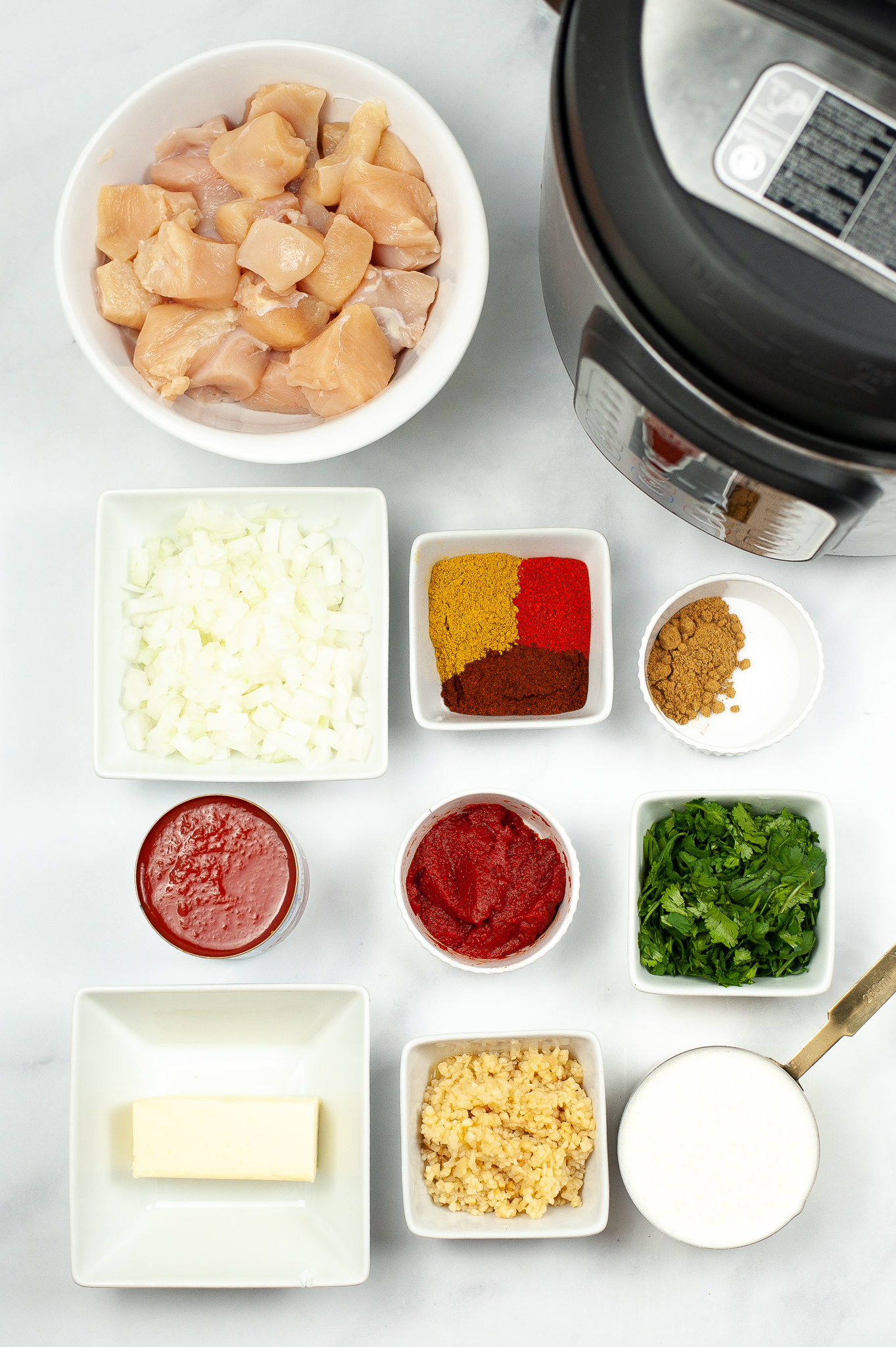Dishes with the ingredients needed to make Instant Pot Butter Chicken. Including Chicken, spices, garlic etc.