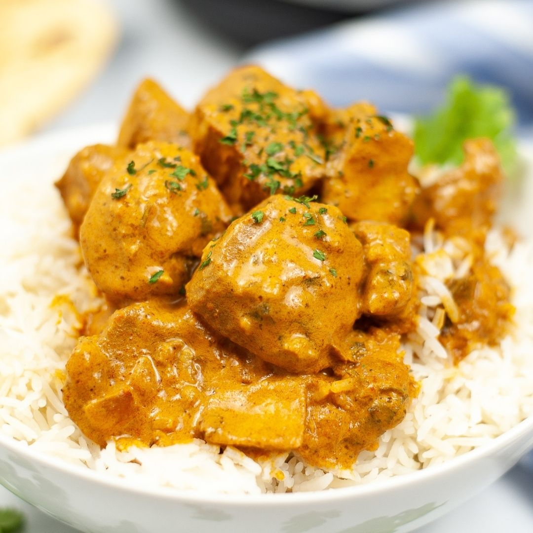 Bowl of Easy butter chicken with fresh herbs on top.