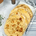 Tray of finished Naan bread with a blue and white stripped napkin.