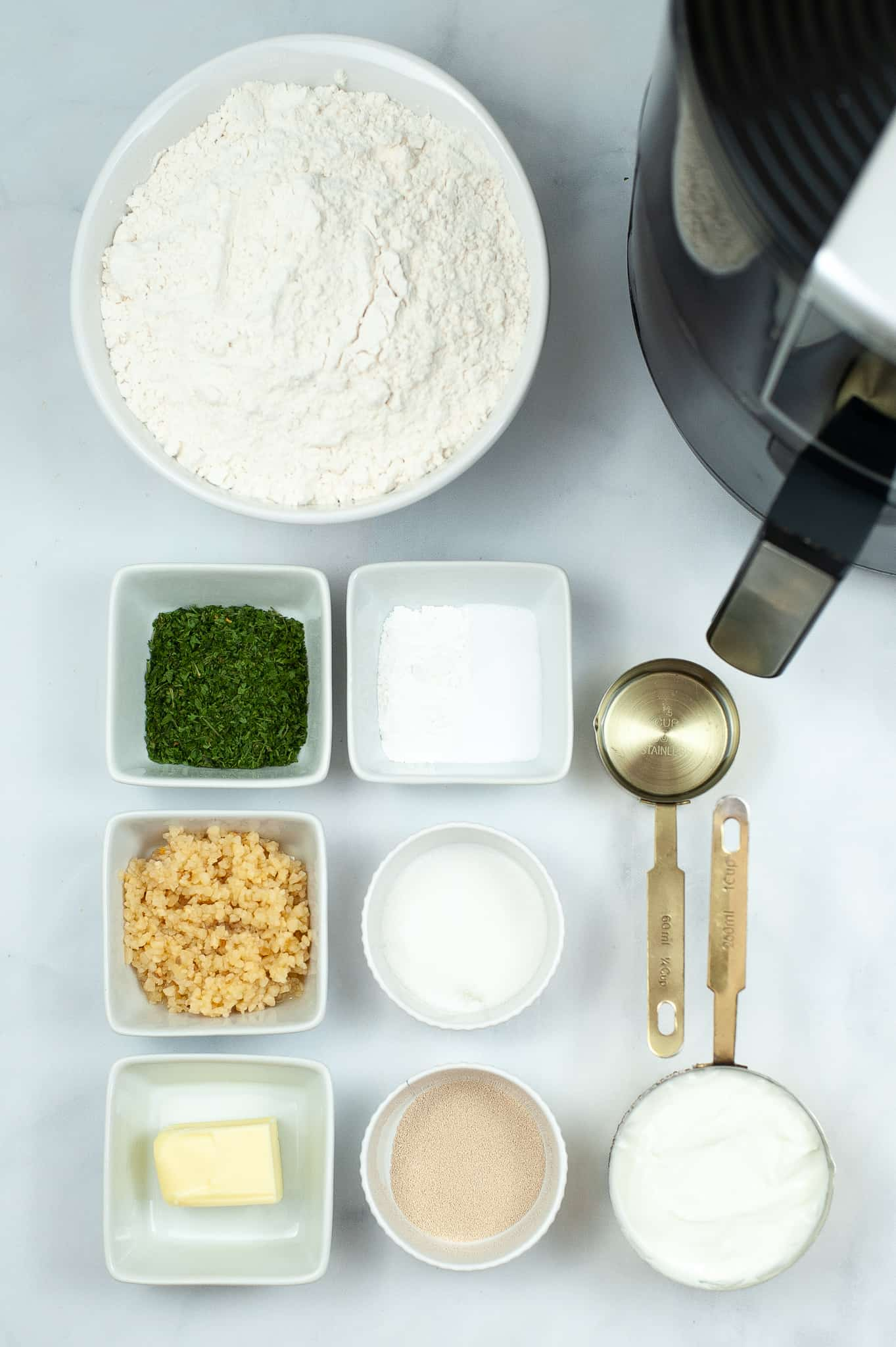 Bowl of flour with seasonings and garlic to make naan bread.