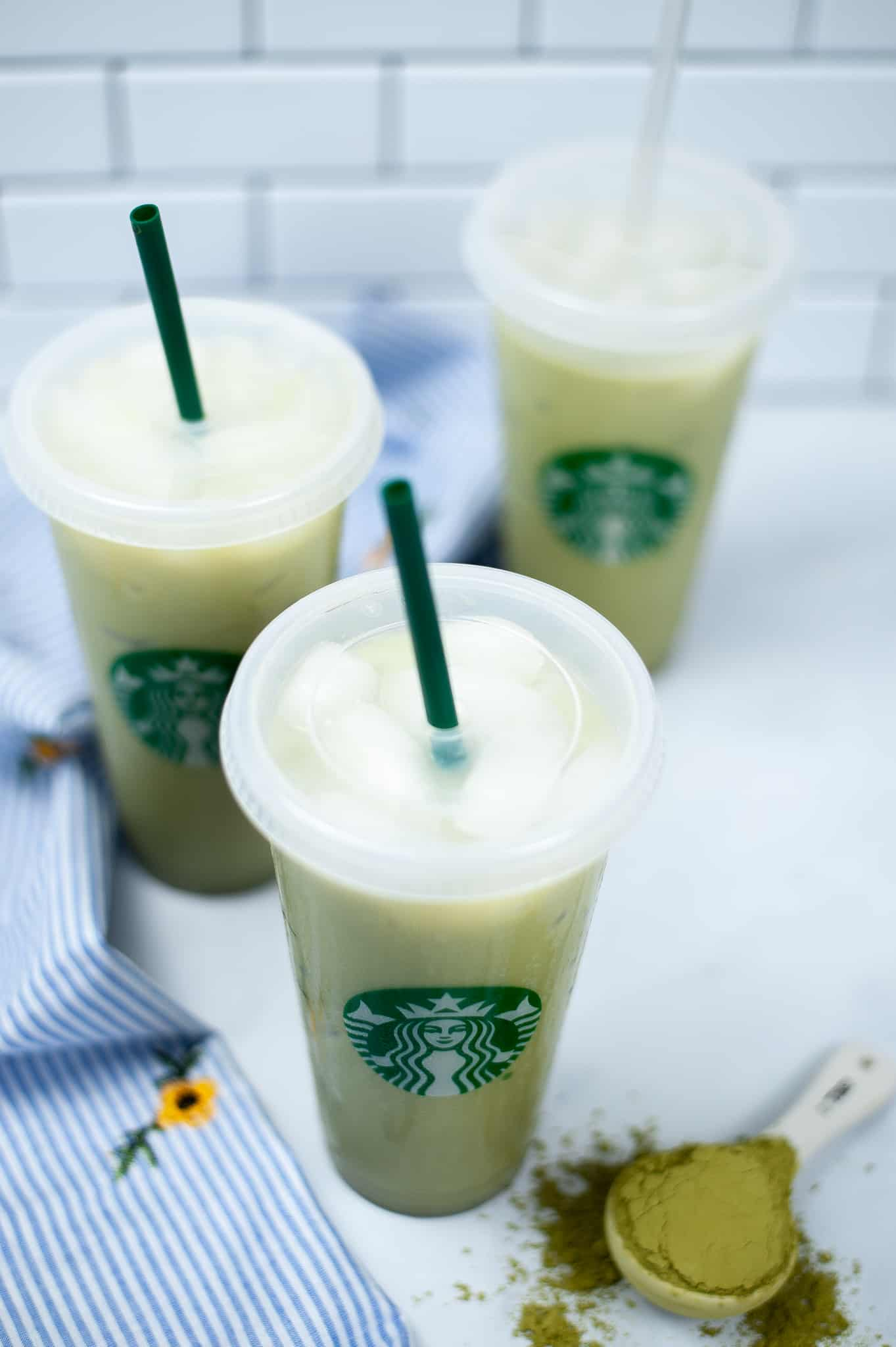 Top shot of 3 matcha lattes with green straws.