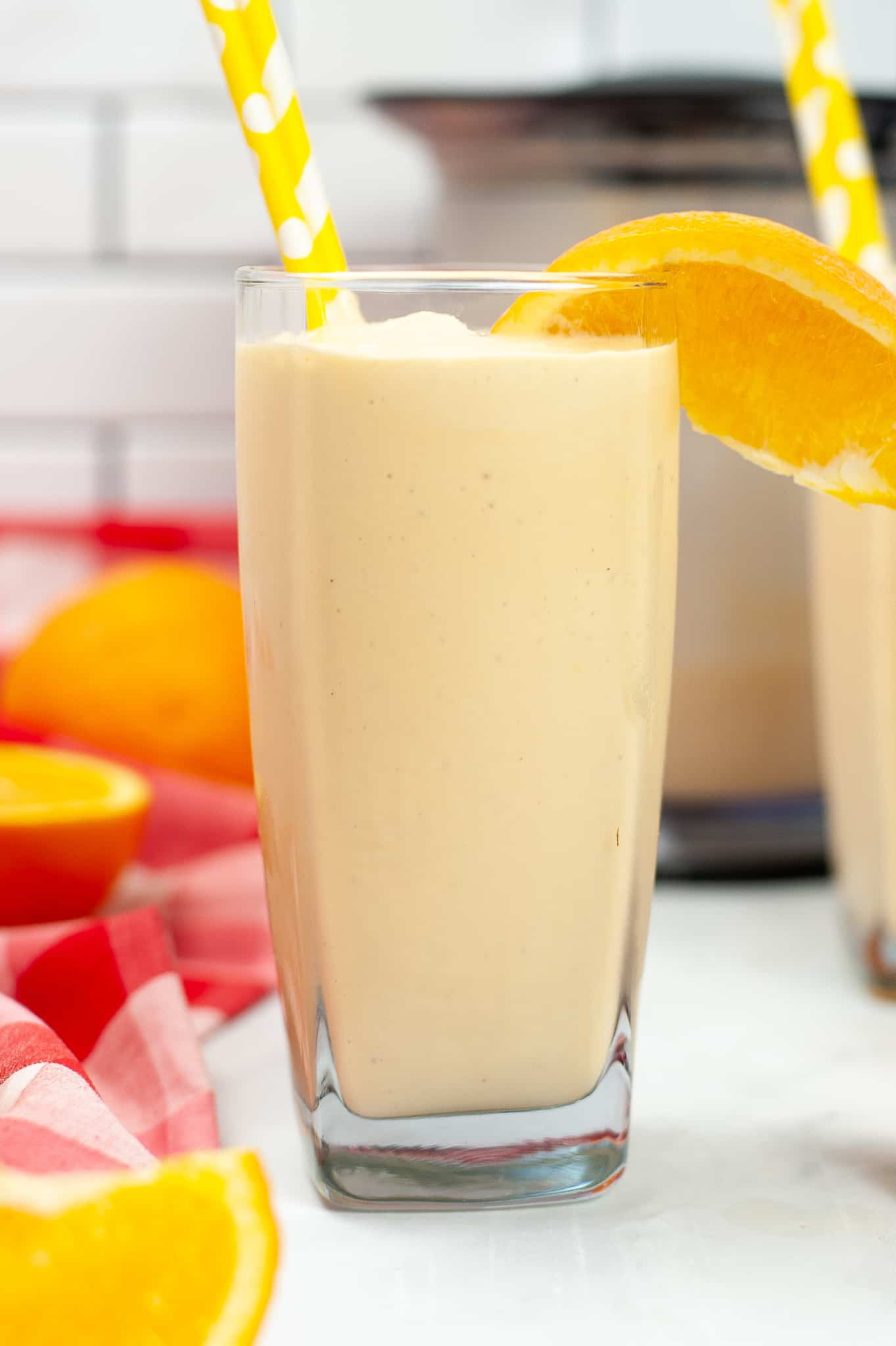 A tall clear glass filled with orange creamsicle Milkshake with a slice of orange in it.