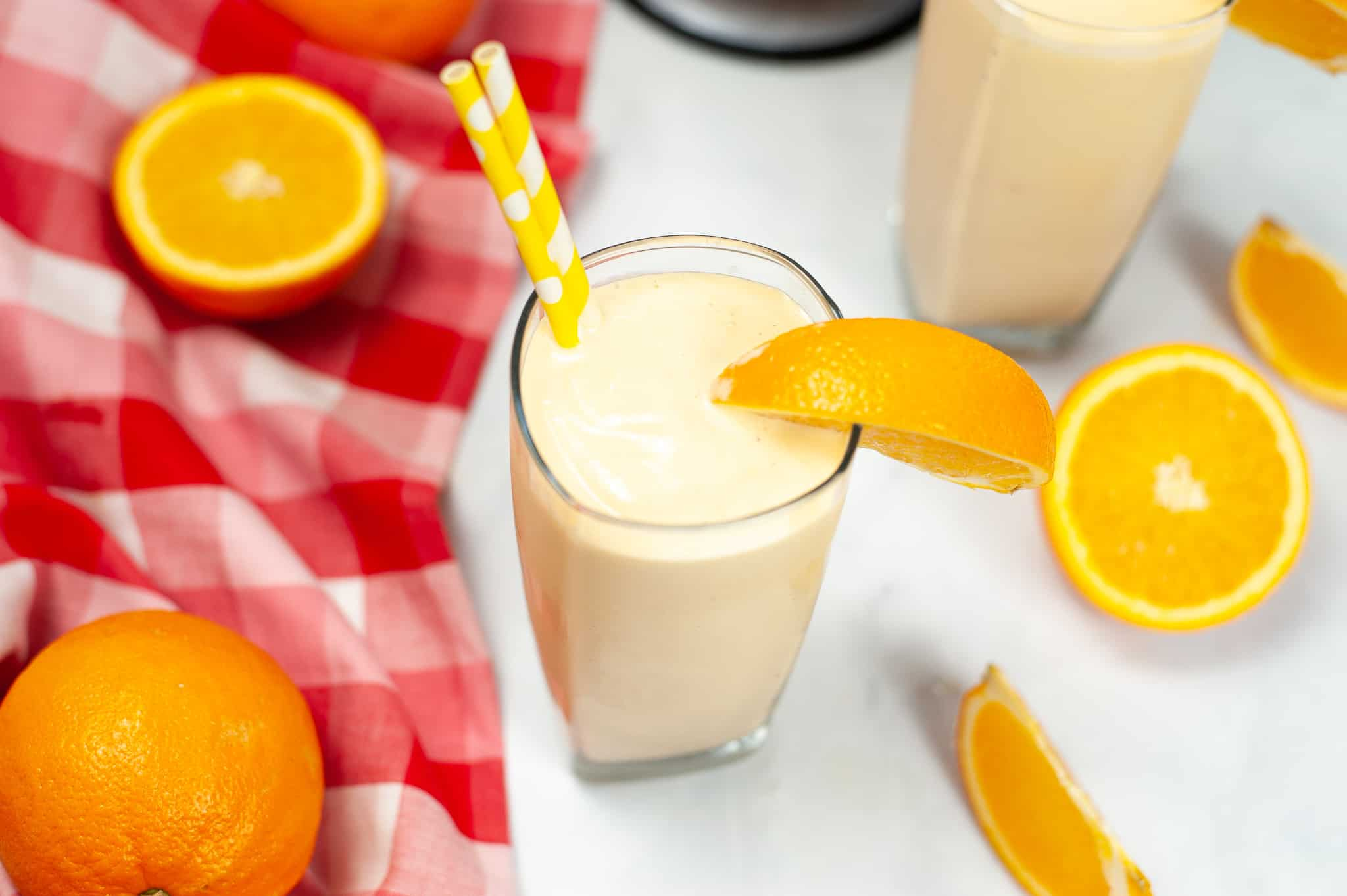 Red and white check napkin with slices of orange and two orange creamsicle milkshakes.