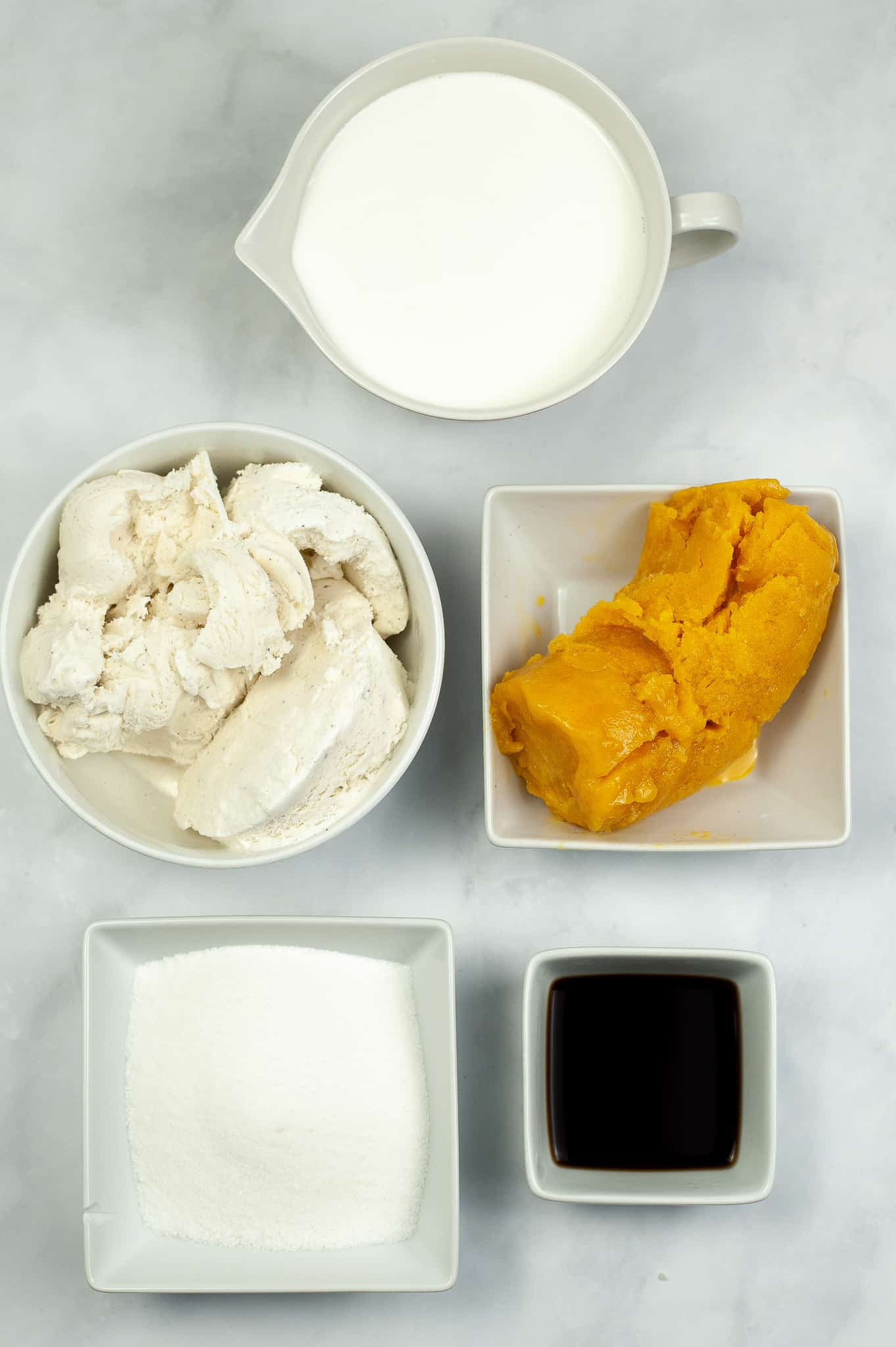 Ingredients in square white dishes for creamsicle milkshake.
