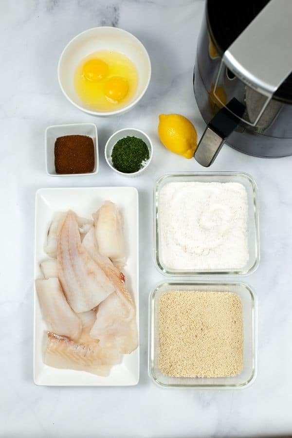 Plates of fish, flour egg and ingredients required for air fryer fish sticks.