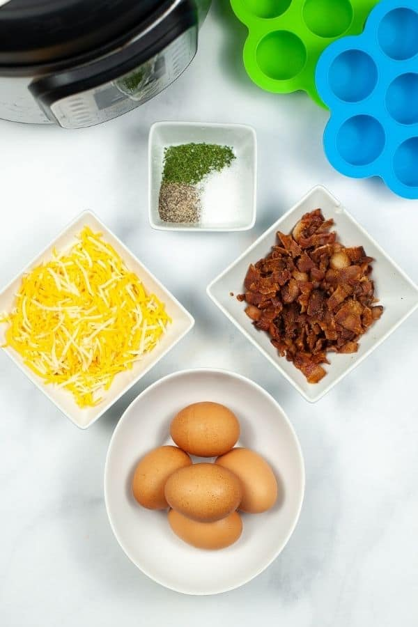 White bowls of eggs, bacon, cheese, and herbs.