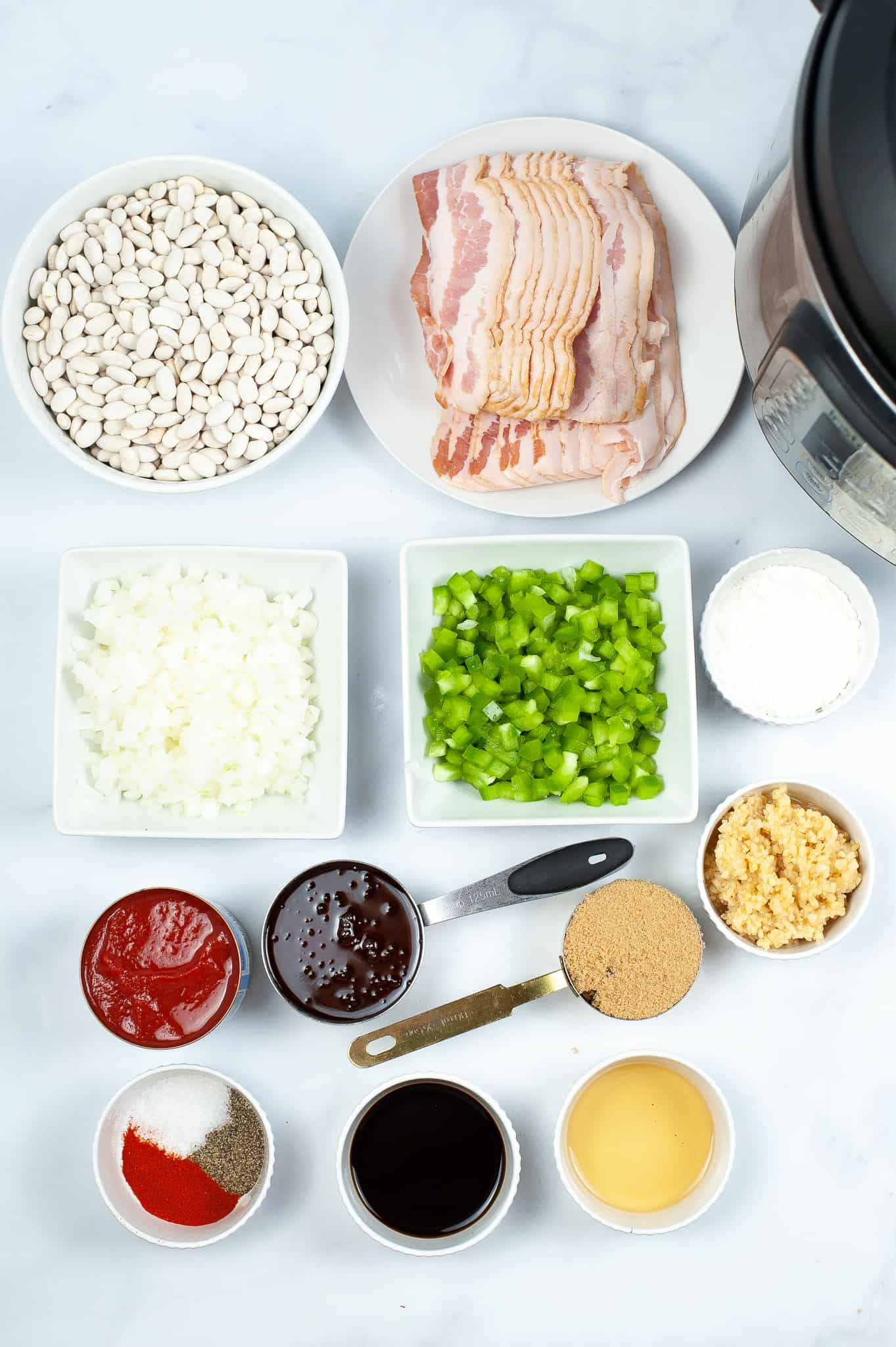 Bowls of beans vegetables bacon and seasonings required to make the instant pot baked beans.