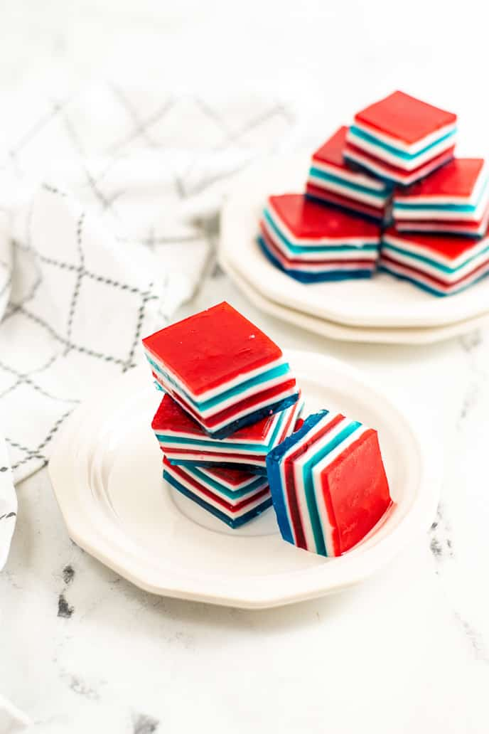 Two plates of layered red white and blue stacked jello with a grey and white checked napkin.