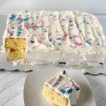 Slice of Homemade Vanilla Cake on a white plate alongside a full cake.