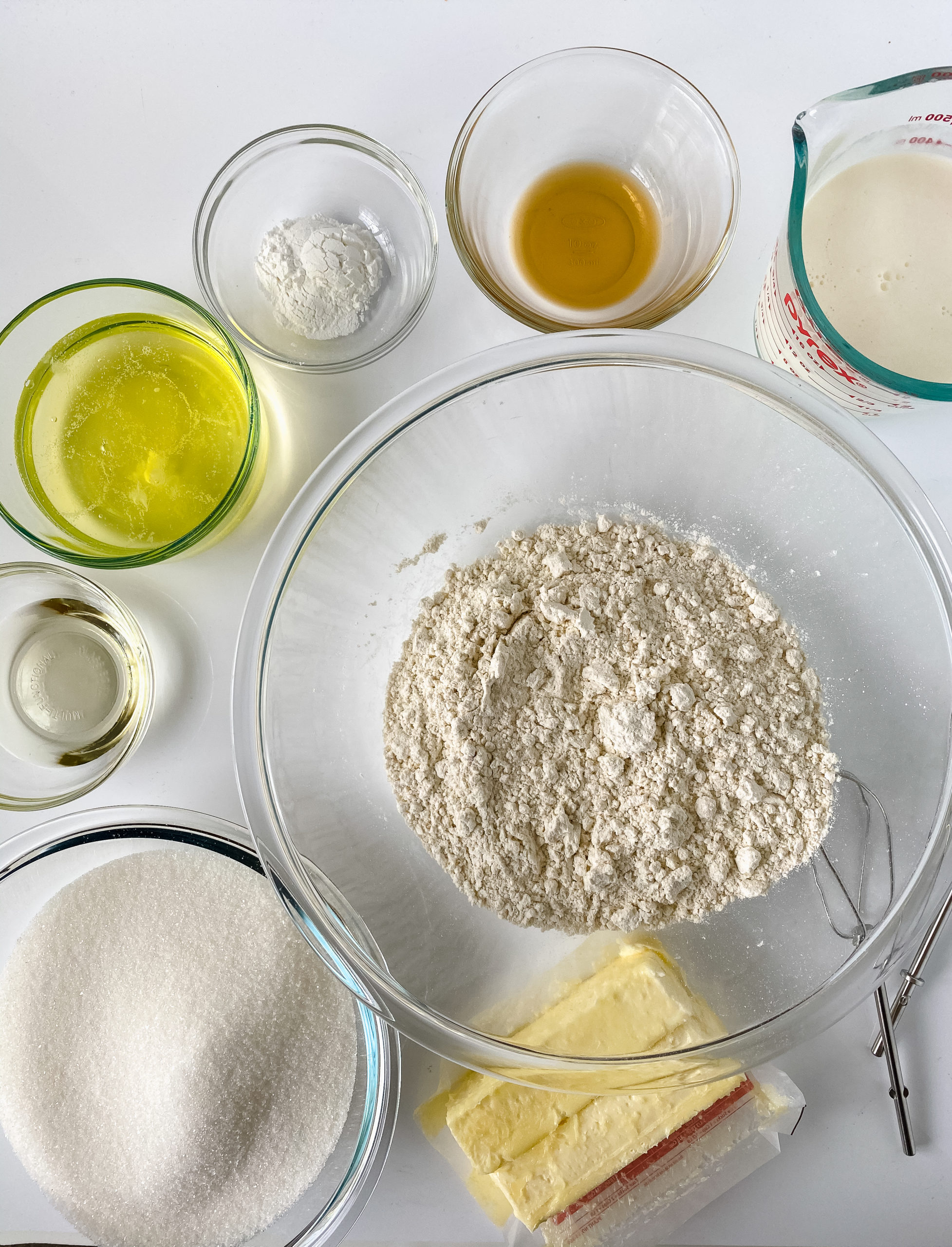 Ingredients in clear bowls for cake. Flour, oil, sugar vanilla. etc.