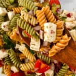 Top shot of tri colored pasta salad in a clear bowl.