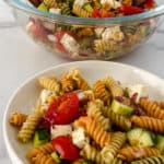 Small with bowl of tri color pasta salad in the foreground and a clear larger bowl of salad in the background.