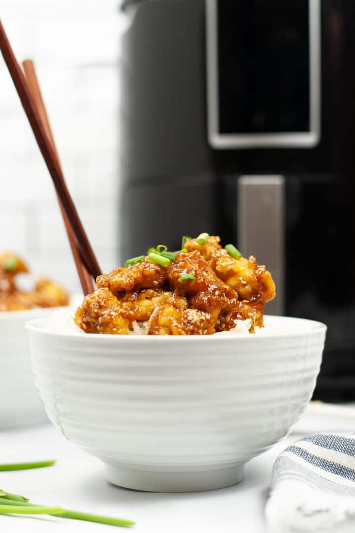 Sesame Chicken in a bowl with chop sticks sticking out.