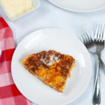 Slice of Instant Pot Lasagna on a round white dish with a fork and check napkin.