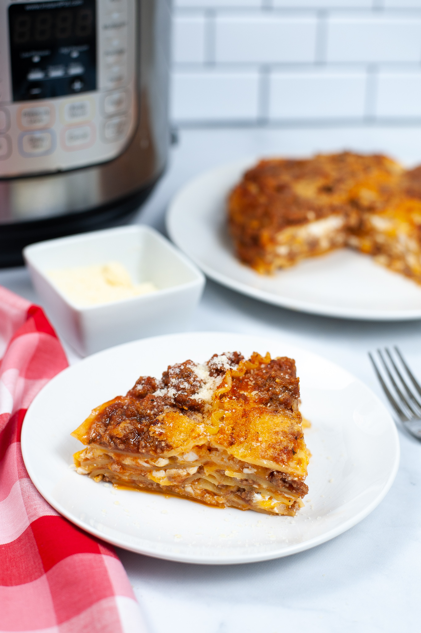 View of Instant Pot Lasagna with slice taken out and instant pot in the background.