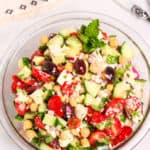 Clear glass bowl filled with Peasant salad on a white tablecloth.
