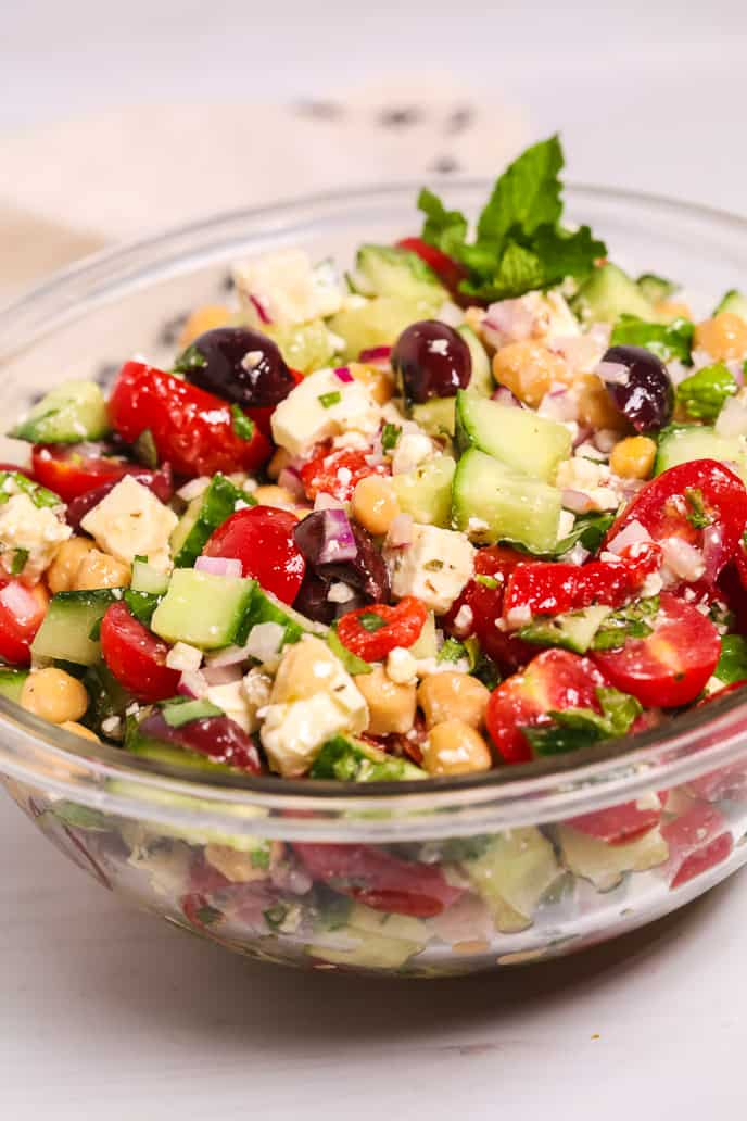 Side view of a clear bowl displaying Peasant Salad.
