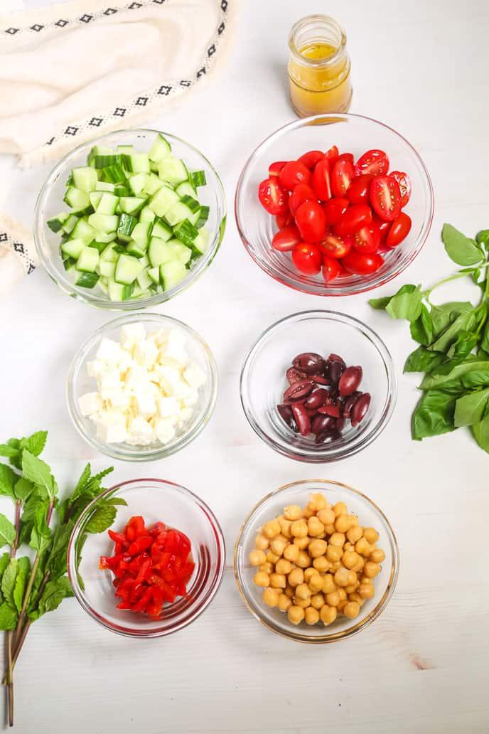 Peasane salad ingredients in clear dish.