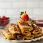 Wide shot of Strawberry Stuffed French Toast with a Whole Strawberry on top.